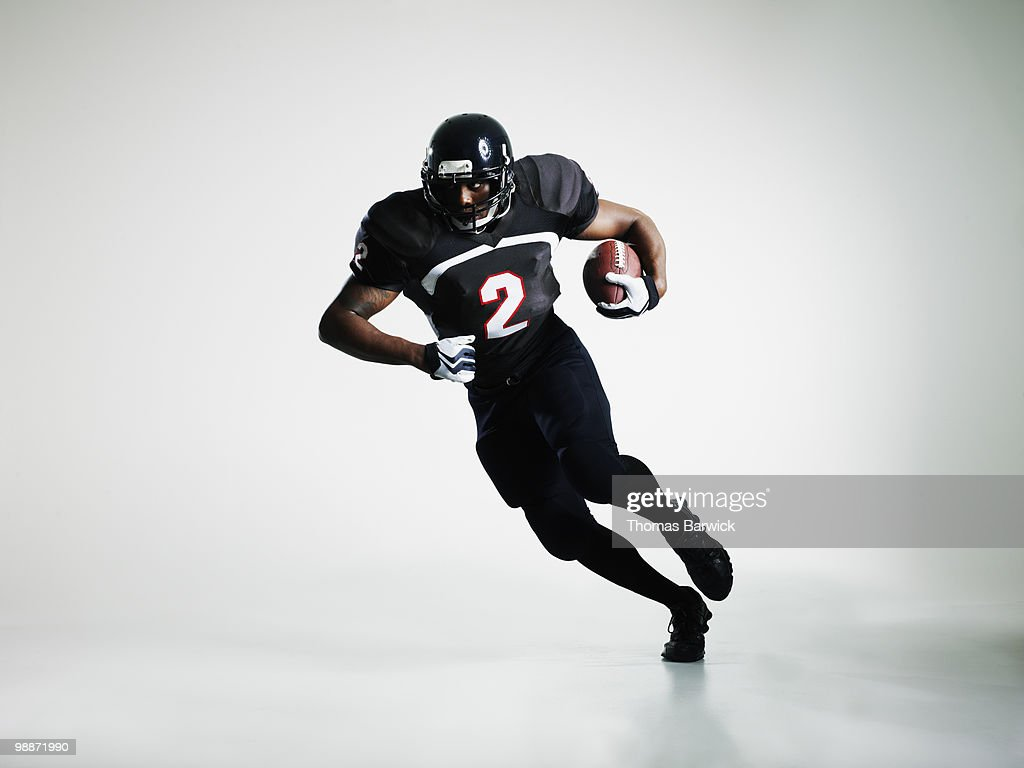 Football player running with ball : Stock Photo