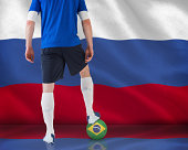 Composite image of football player standing with ball against digitally generated russian national flag