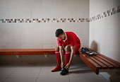 Football player tying shoe, alone in changing room