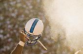 Football player waving helmet in air.