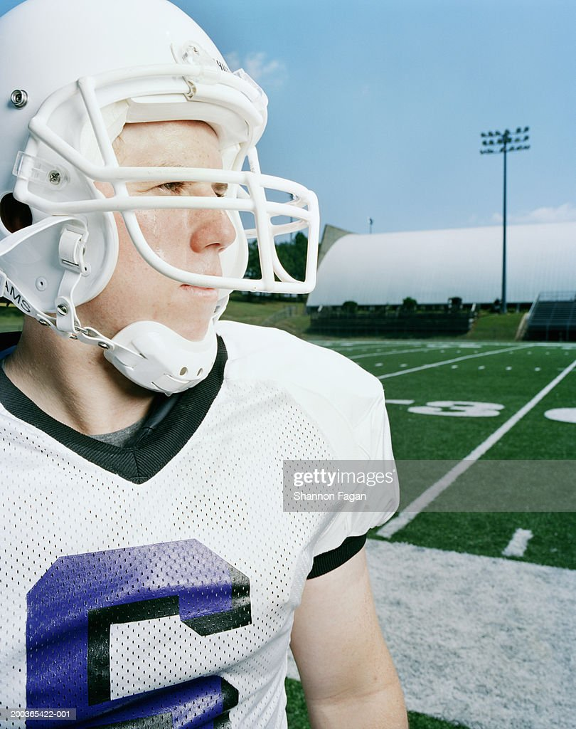 Football player wearing helmut, looking away : Stock Photo