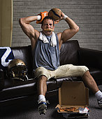 Football player with pizza in mouth looking frustrated
