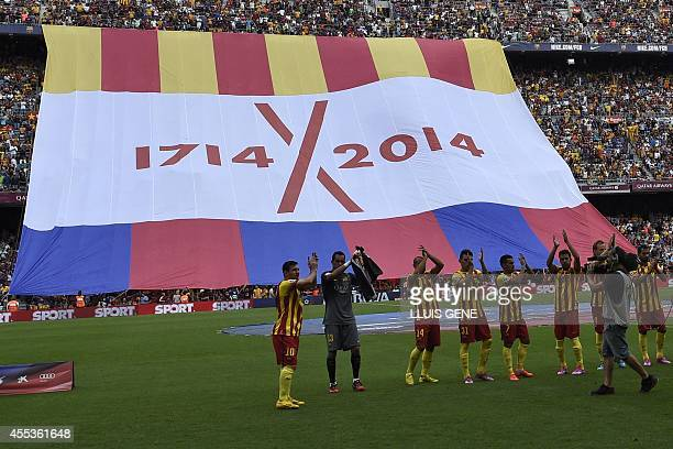 Football players applaud as proindepence fans display a giant flag in support of Catalonia's independence during the Spanish league football match FC...