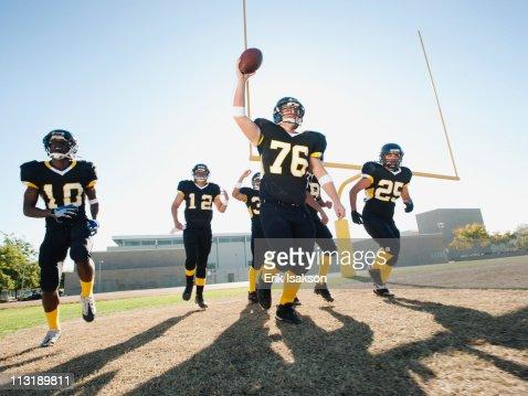 Football players celebrating on football field