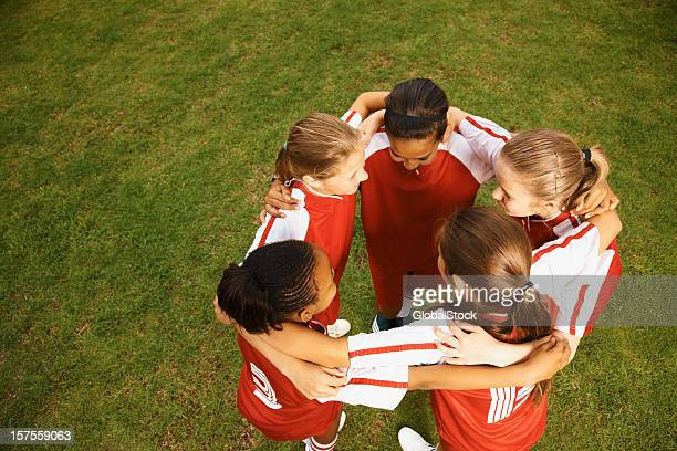 Football players forming a huddle before the match