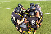 Football players huddled together before play on field