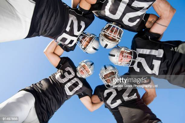 Football players in huddle