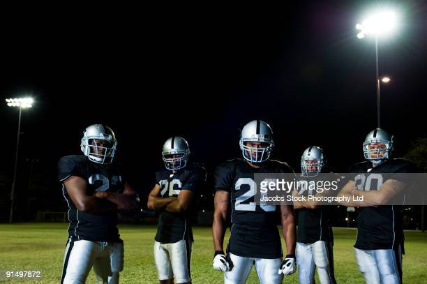 Football players in uniform with arms crossed