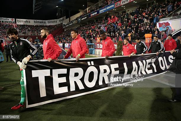 Football players of Trabzonspor and Besiktas hold a banner which condemn terrorism before Turkish Spor Toto Super Lig football match between...