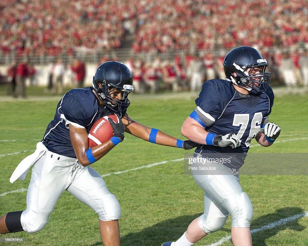 Football players passing ball