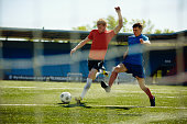 Two young sportsmen playing football
