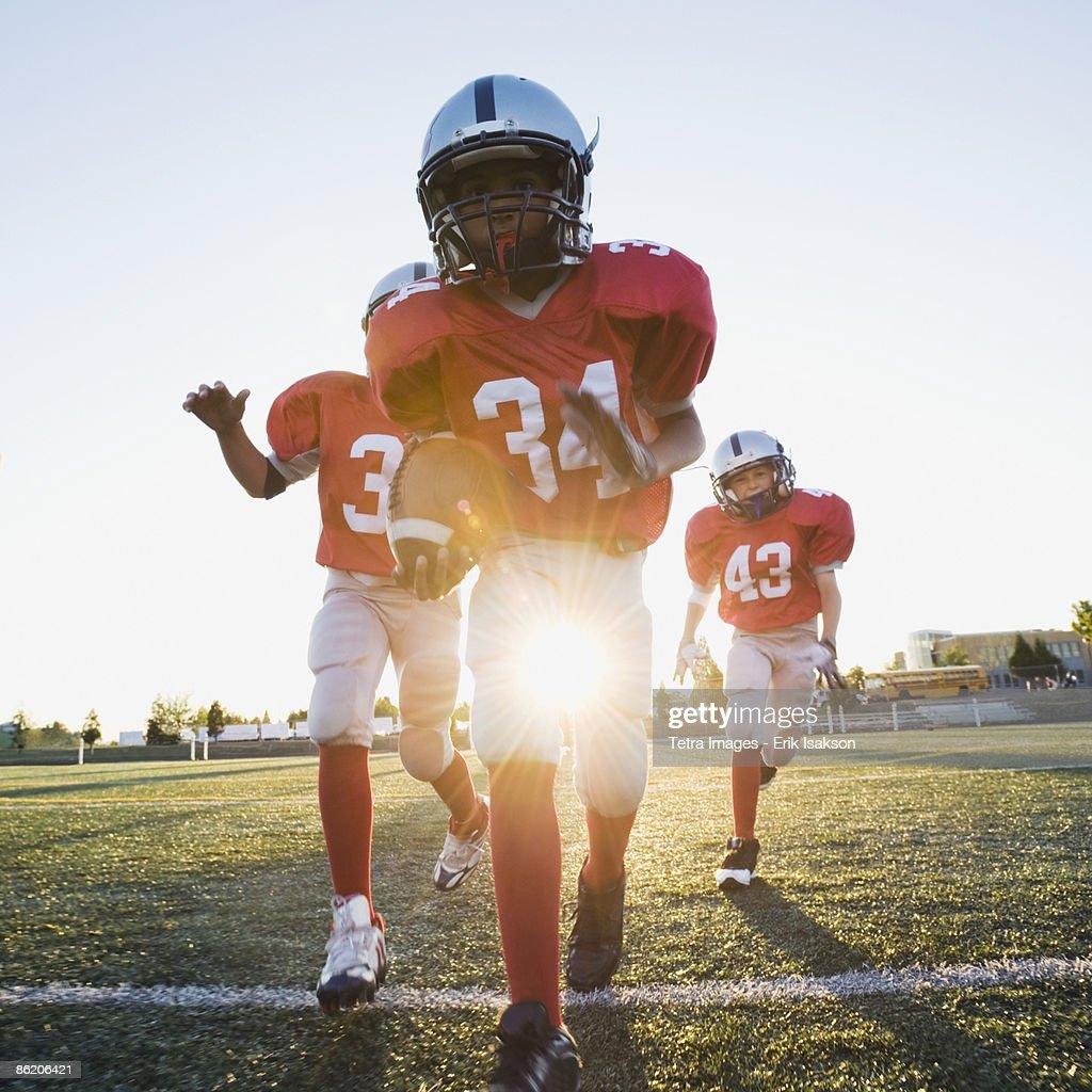 Football players running on field : Stock Photo