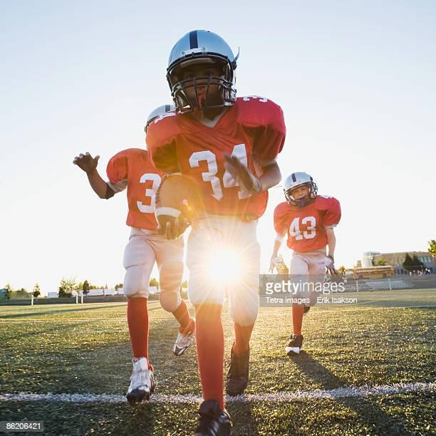 Football players running on field