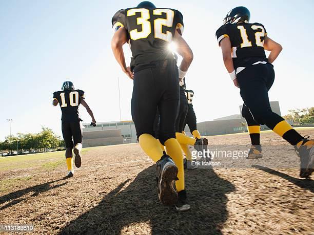 Football players running on football field