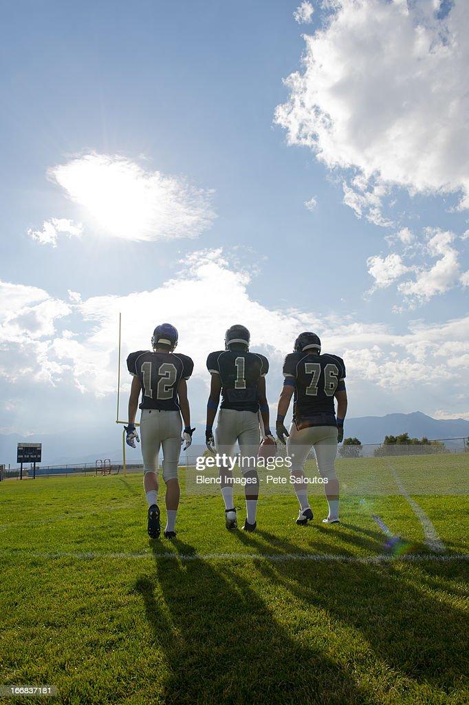 Football players walking on field