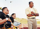 Football players with coach, watching game from side lines