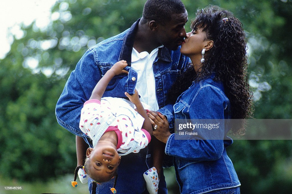 Portrait of Dallas Cowboys Michael Irvin kissing wife Sandy and holding daughter Myesha during photo shoot. Bill Frakes F30 )