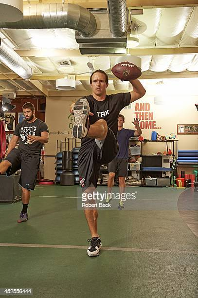 Portrait of New Orleans Saints QB Drew Brees demonstrating dynamic warmup exercise with Cleveland Browns Tank Carder and Saints backup QB Ryan...
