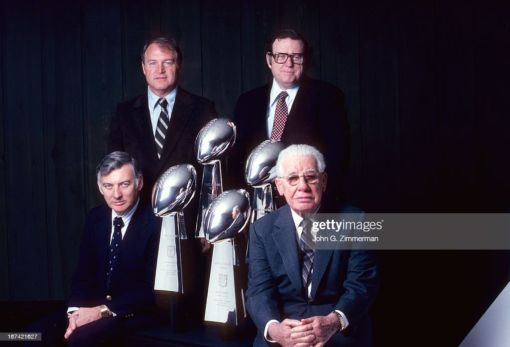 Portrait of Pittsburgh Steelers front office (L-R) team president Dan Rooney, coach Chuck Noll, team vice president Art Rooney Jr., and owner and chairman Art Rooney Sr. with four Vince Lombardi Trophies during photo shoot. John G. Zimmerman