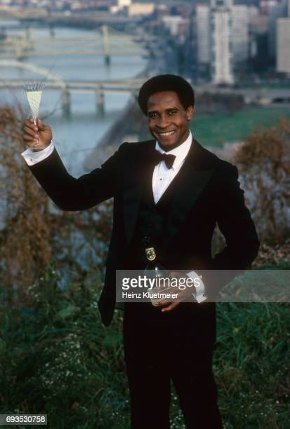 Portrait of Pittsburgh Steelers Lynn Swann casual wearing tuxedo and holding up glass of champagne during photo shoot at Mount Washington Scenic view...