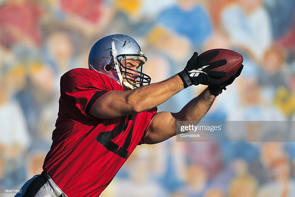 Football receiver catching ball