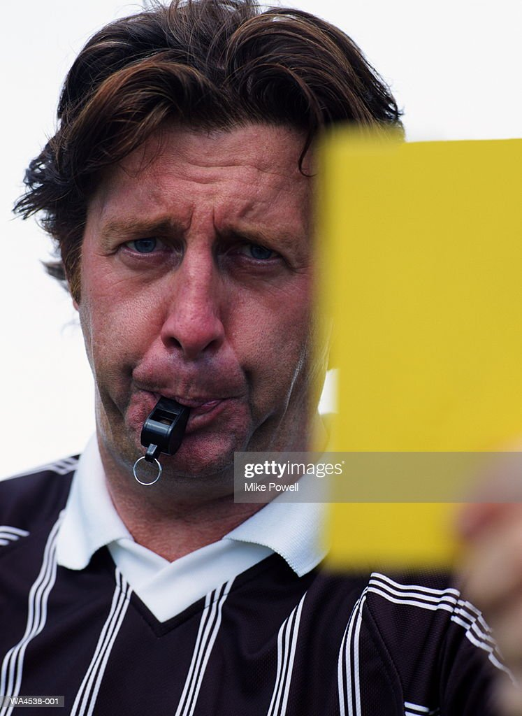 Football, referee blowing whistle and holding yellow card : Stock Photo