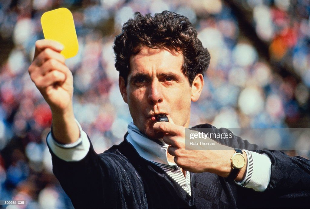 Football referee blowing whistle & holding up yellow card (Composite) : Stock Photo