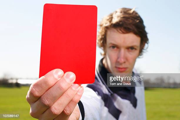 Football Referee Holding up Red Card card in focus