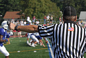 A referee at a North American Football game.  He has his arm extended his whistle and stop watch are visible.  There is an active game with players and spectators in the blurred background