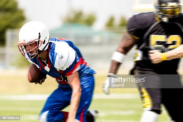 Football running back carries the ball. Defenders. Motion.