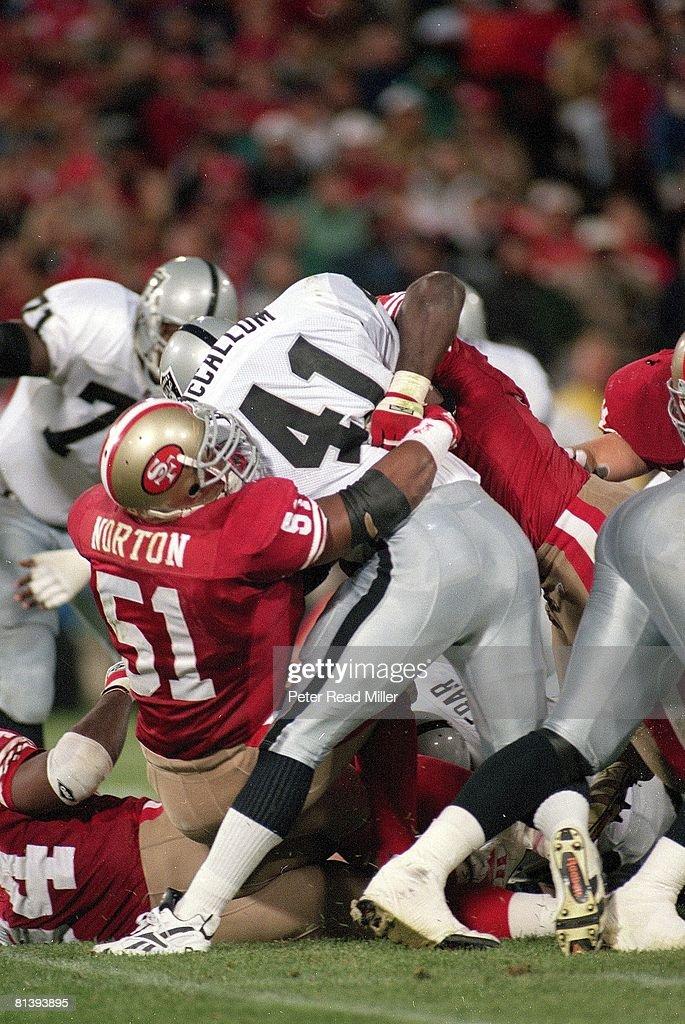 San Francisco 49ers Ken Norton Jr, (51) in action, making tackle during pileup vs Los Angeles Raiders Napolean McCallum (41) sustaining season ending, dislocated knee injury, San Francisco, CA 9/5/1994