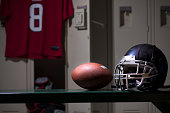 Various sports equipment on bench inside high school or college gymnasium locker room.   Items include: football helmet, ball, pads, jersey.