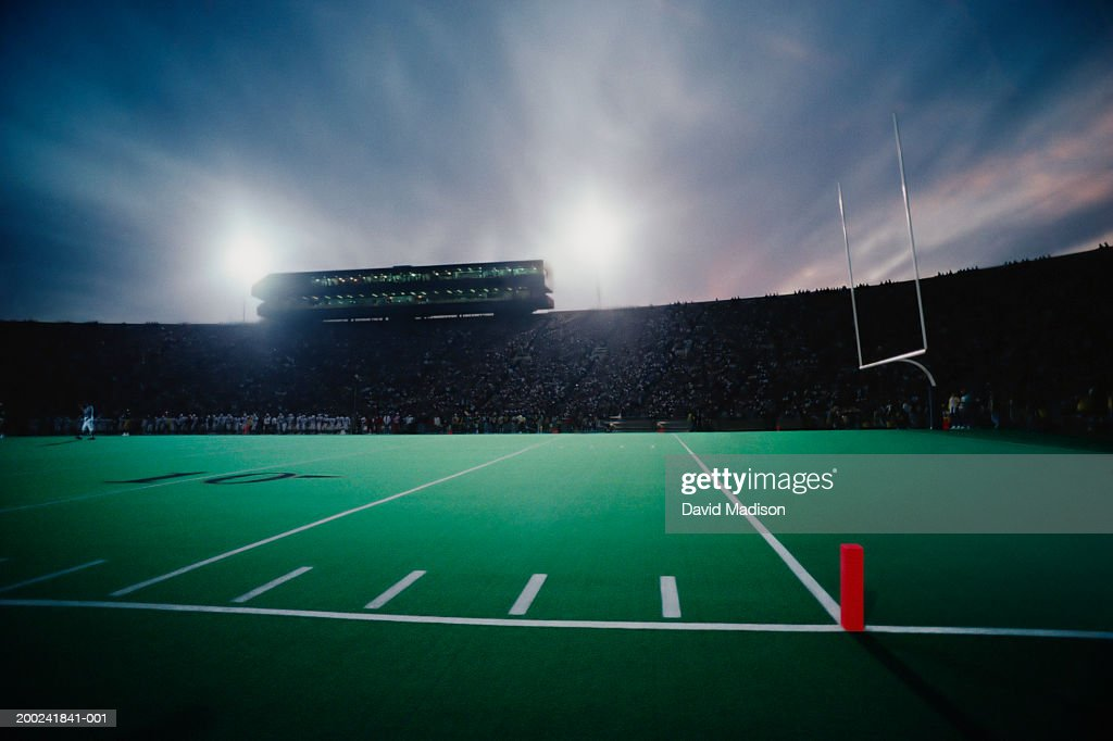 Football stadium filled with spectators during game, twilight : Stock Photo