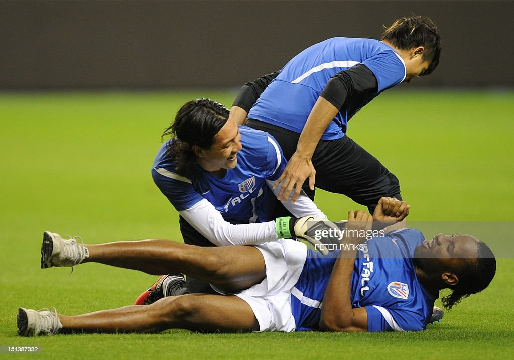 Football star Didier Drogba (bottom) is jumped on by Shanghai Shenhua goalkeeper Dong Guangxiang (C) and defender Xiong Fei (top) before a training session at Hongkou stadium in Shanghai on October 19, 2012. Drogba has injured his right ankle so he will not play the next match for his Chinese club after returning from international duty and into a row that has seen his teammates reportedly refusing to practise over unpaid wages. AFP PHOTO/Peter PARKS