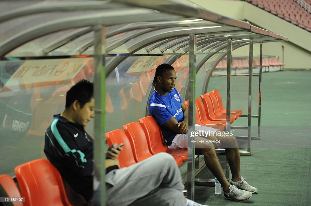 Football star Didier Drogba (R) sits on the bench as his Shanghai Shenhua team mates warm up before a training session at Hongkou stadium in Shanghai on October 19, 2012. Drogba has injured his right ankle so he will not play the next match for his Chinese club after returning from international duty and into a row that has seen his teammates reportedly refusing to practise over unpaid wages. AFP PHOTO/Peter PARKS