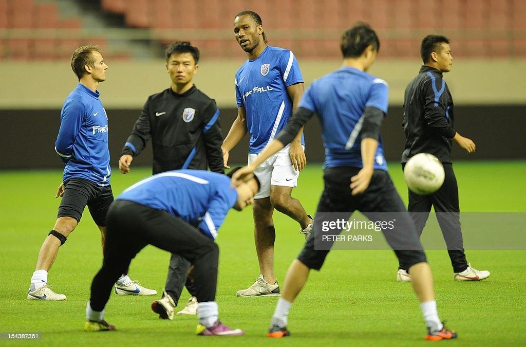 Football star Didier Drogba watches as his Shanghai Shenhua team mates warm up before a training session at Hongkou stadium in Shanghai on October 19...