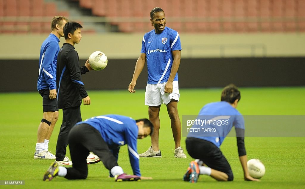 Football star Didier Drogba (C) watches as his Shanghai Shenhua team mates warm up before a training session at Hongkou stadium in Shanghai on October 19, 2012. Drogba has injured his right ankle so he will not play the next match for his Chinese club after returning from international duty and into a row that has seen his teammates reportedly refusing to practise over unpaid wages. AFP PHOTO/Peter PARKS