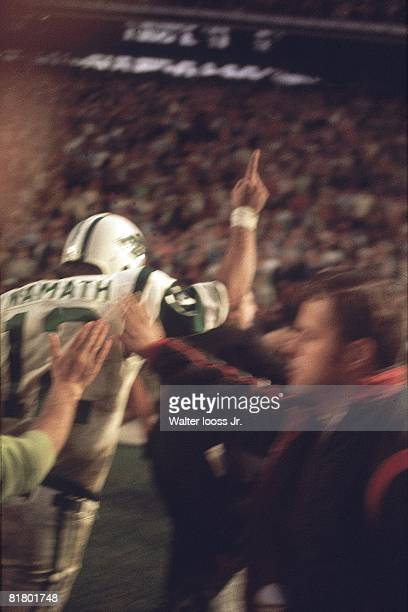 Football Super Bowl III Rear view of New York Jets QB Joe Namath victorious leaving field and gesturing number 1 after winning game vs Baltimore...