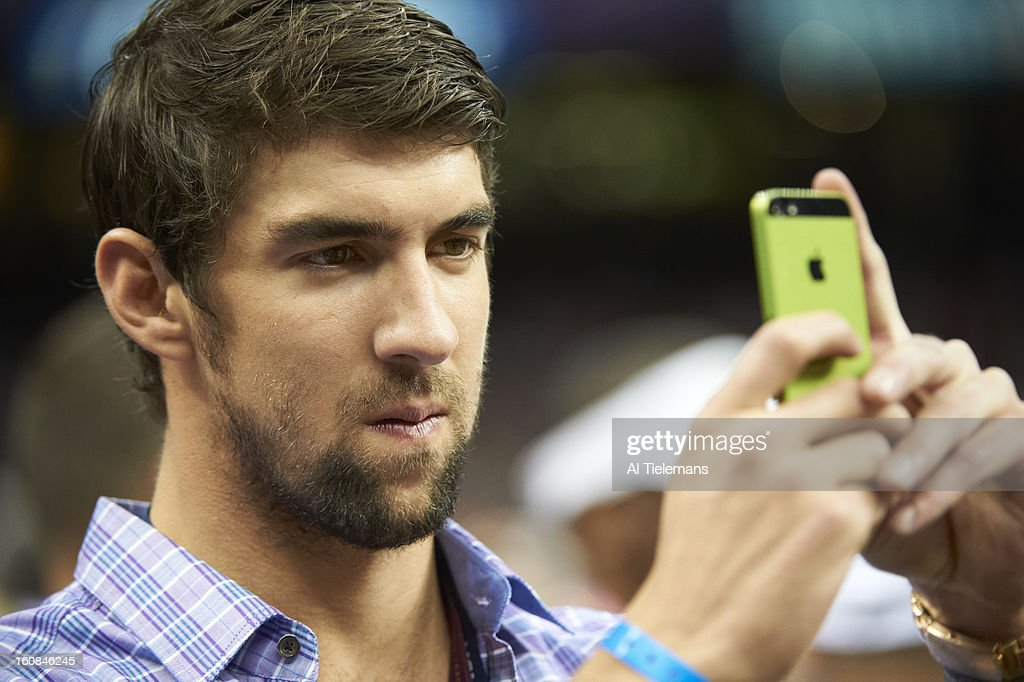 Closeup of Baltimore Ravens fan Michael Phelps taking picture with the camera on his iPhone during game vs San Francisco 49ers at Mercedes-Benz Superdome. Al Tielemans F10 )