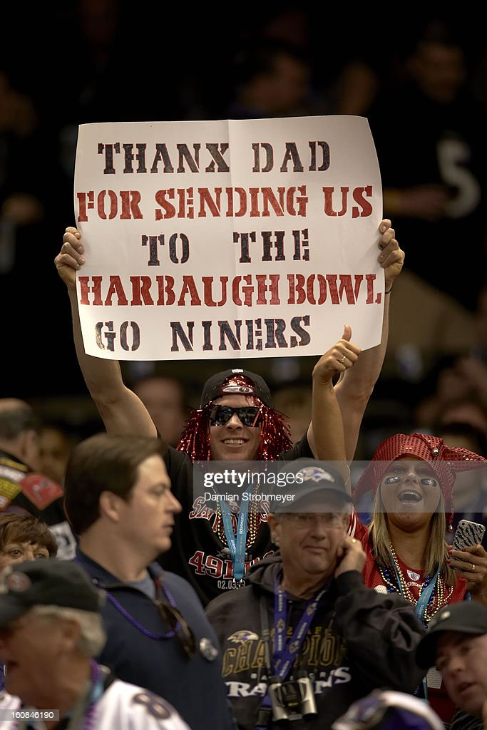 San Francisco 49ers fan holding sign reading THANX DAD FOR SENDING US TO THE HARBAUGH BOWL GO NINERS during game vs Baltimore Ravens game at Mercedes-Benz Superdome. Damian Strohmeyer F59 )