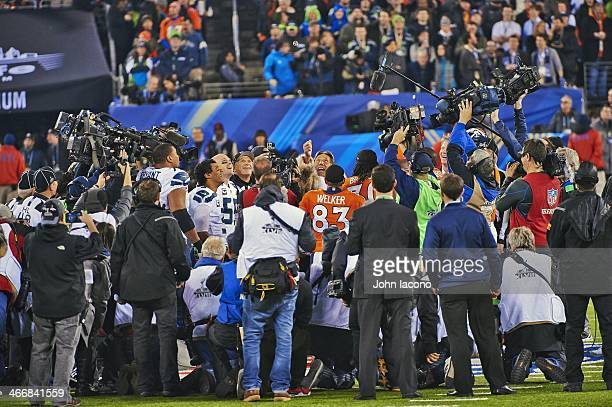 Super Bowl XLVIII Former New York Jets QB Joe Namath surrounded by players officials media during coin toss as Seattle Seahawks QB Russell Wilson and...