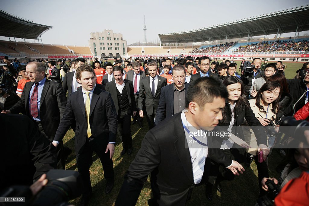 Football superstar David Beckham (C) arrives for a promotional event in Tiantai Stadium in Qingdao, east China's Shandong province on March 22, 2013. Beckham raised the prospect of one last stop on his global football journey, refusing to rule out playing in China after his contract with Paris Saint-Germain ends. CHINA