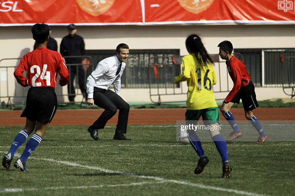 Football superstar David Beckham plays with a group of Chinese youngsters during a promotional event in Tiantai Stadium in Qingdao, east China's Shandong province on March 22, 2013. Beckham raised the prospect of one last stop on his global football journey, refusing to rule out playing in China after his contract with Paris Saint-Germain ends. CHINA