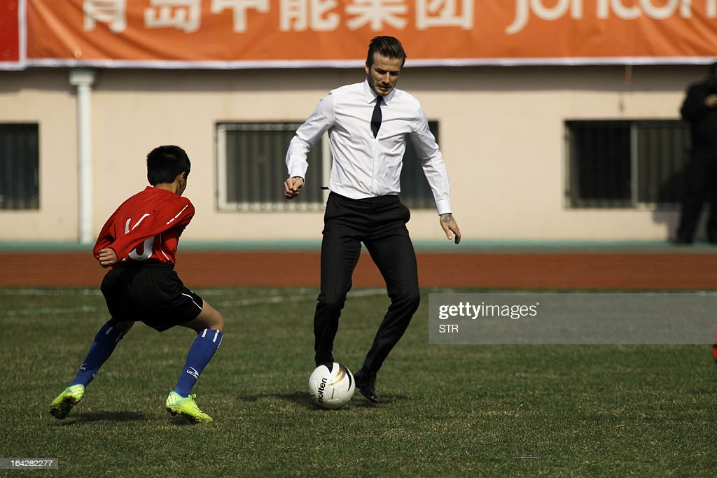 Football superstar David Beckham plays with a group of Chinese youngsters during a promotional event in Tiantai Stadium in Qingdao, east China's Shandong province on March 22, 2013. Beckham raised the prospect of one last stop on his global football journey, refusing to rule out playing in China after his contract with Paris Saint-Germain ends. CHINA OUT AFP PHOTO