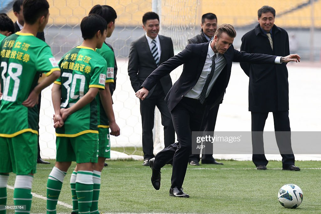Football superstar David Beckham (C) teaches young players during a visit to Beijing Guoan soccer club in Beijing on March 21, 2013. Beckham flew to Beijing on March 20 to take up a role as ambassador for the Chinese Super League, with domestic media saying he will visit three cities on a five day trip.