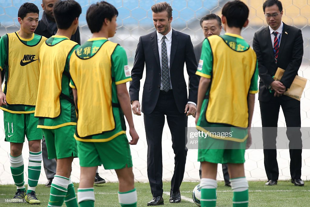 Football superstar David Beckham (C) teaches young players during a visit to Beijing Guoan soccer club in Beijing on March 21, 2013. Beckham flew to Beijing on March 20 to take up a role as ambassador for the Chinese Super League, with domestic media saying he will visit three cities on a five day trip. AFP PHOTO CHINA OUT
