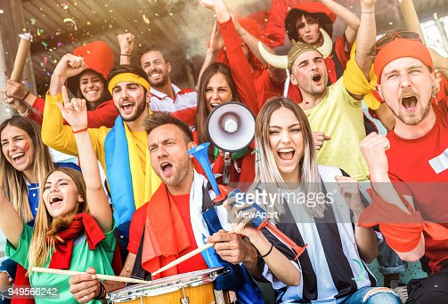 Football supporter fans friends cheering and watching soccer cup match at intenational stadium - Young people group with multicolored t-shirts having excited fun on sport world championship concept : Stock Photo