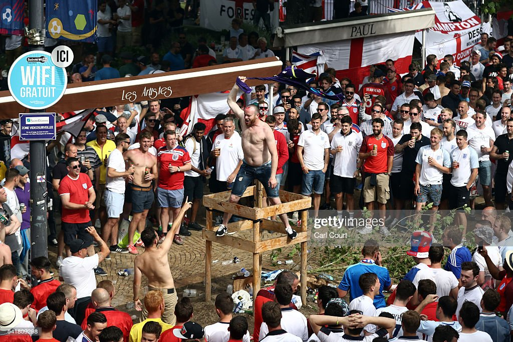 a football supporter waves his shirt as england and slovakia fans enjoy a street party ahead