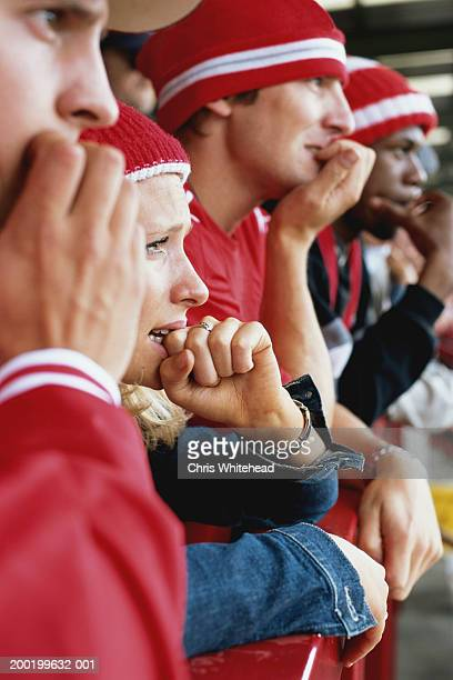 Football supporters at match, biting nails, side view, close-up