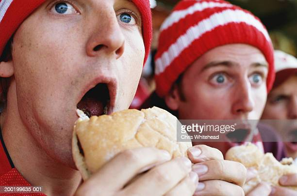 Football supporters at match, holding hambugers, gasping